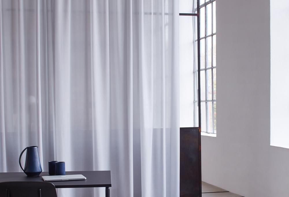 """Wohnlich und funktional: Der transparente Vorhang """"Sinfoniacoustic"""". Abbildung: © Création Baumann"""