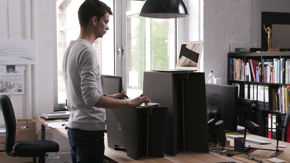 Laptop und Tastatur werden auf verschieden hohe Ebenen gestellt.