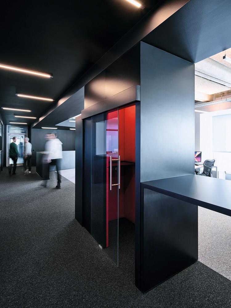 Coole Arbeitsplätze: Rot gepolsterte Telefonzellen im schwarzen Durchgang. Foto: Mark Seelen for de Winder