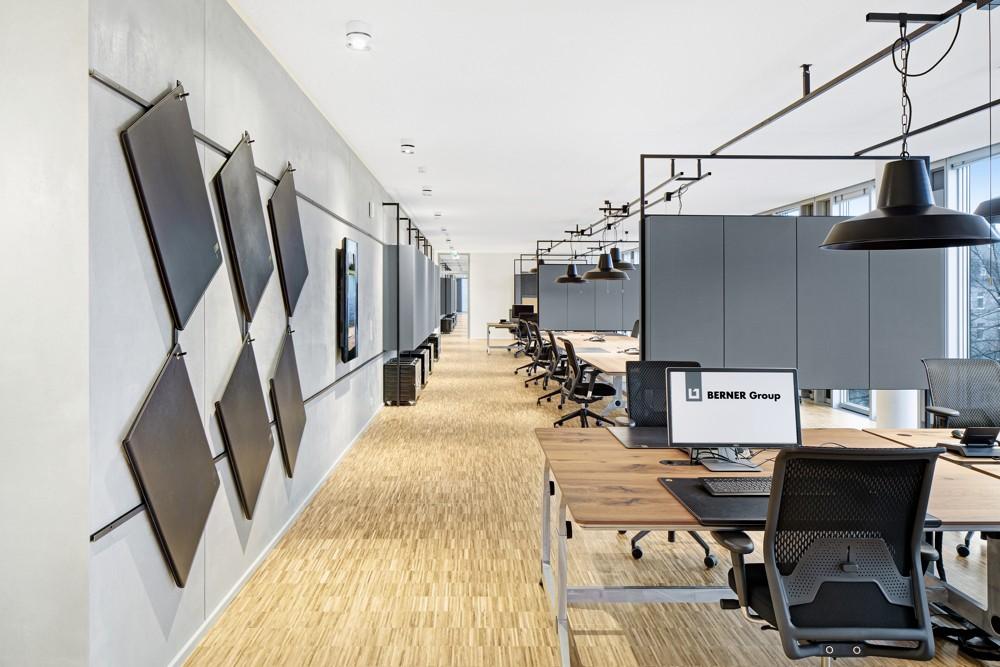 Konstruktionen aus Vierkantstahl unterstützen die Leuchtenaufhängung und sind Rahmen für Zonierungsmodule sowie Regale. Fotos: hell und freundlich/Lukas Palik Fotografie