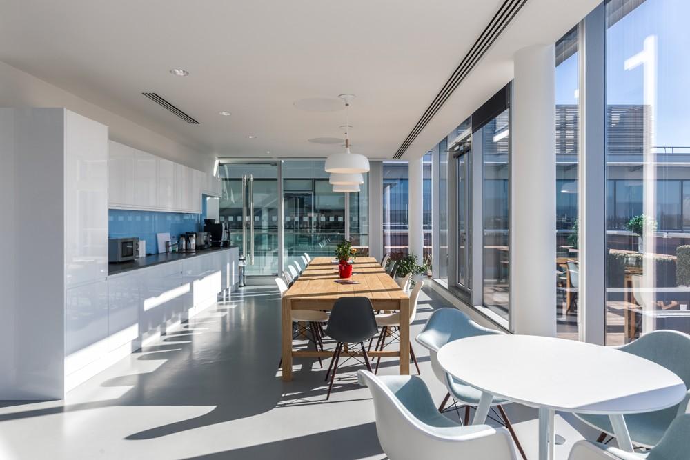 Küchenbereich mit großem Esstisch und Zugang zur Terrasse. Foto: Adam Woodward