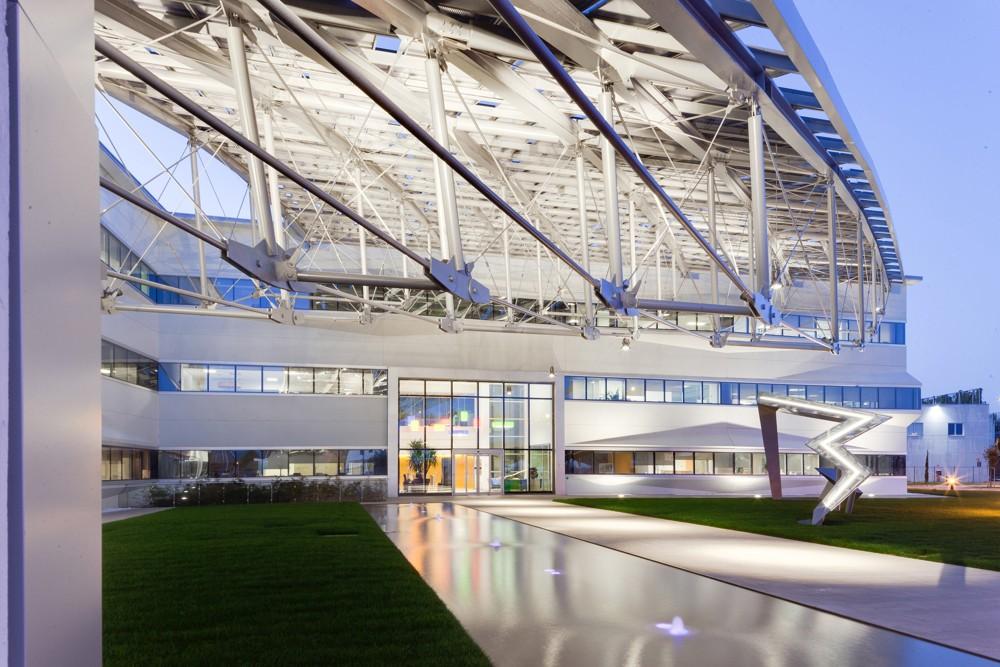 Große Dachflügel mit Solarzellen schließen sich seitlich an das Gebäude an.