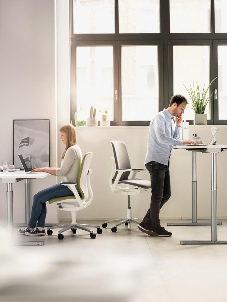 AT-Modelle mit erhöhter Sitzposition und zuschaltbarer Vorneigung fördern den Wechsel zwischen Sitzen und Stehen an höhenverstellbaren Arbeitsplätzen.