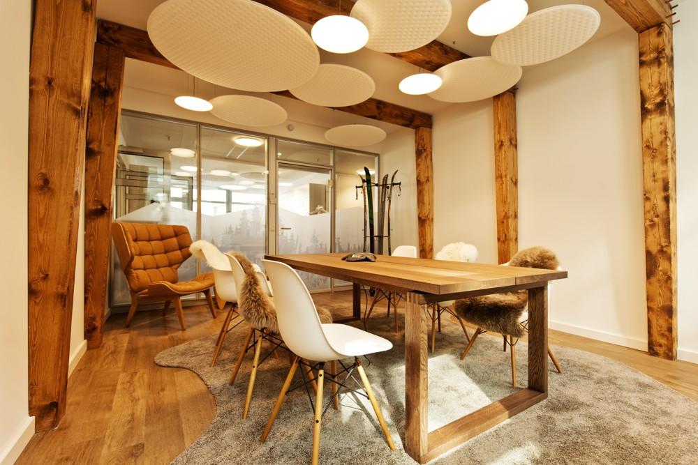 Besprechungsraum mit sichtbaren Holzbalken, kuscheligem Teppich und einer Garderobe aus alten Skiern
