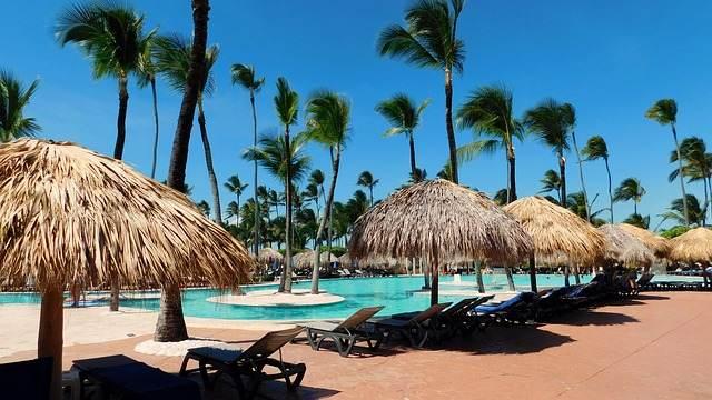 Weißer Sandstrand mit Palmen und Sonnenschirmen in der Karibik. Abbildung: Pixabay