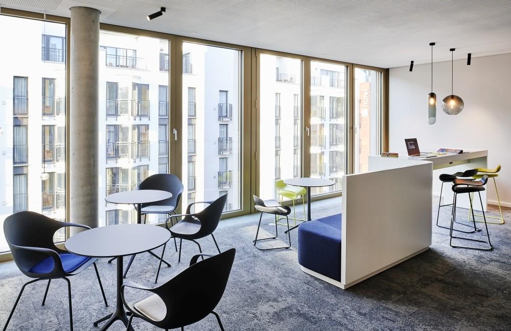 Designerleuchten und hochwertige Möbel setzen in den Kommunikationszonen Akzente. Abbildung: Joachim Grothus, Brandherm + Krumrey