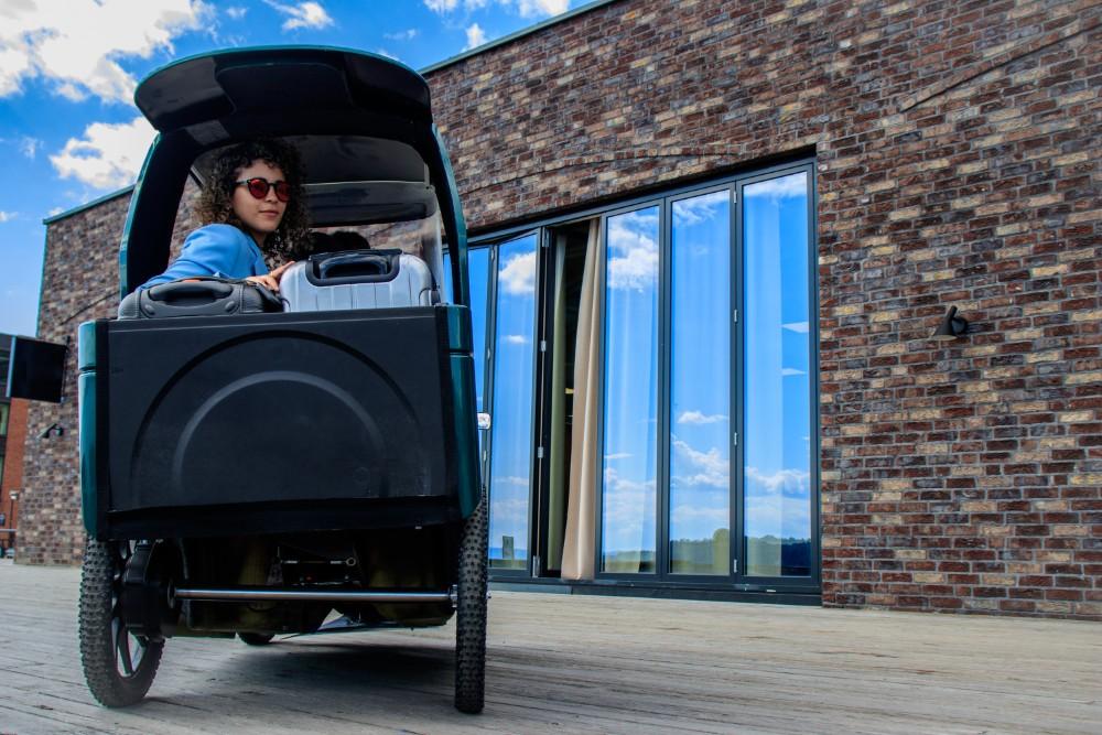 Das E-Bike besitzt ein Dach, Türen und hat Platz für Passagiere und Fracht. Abbildung: CityQ