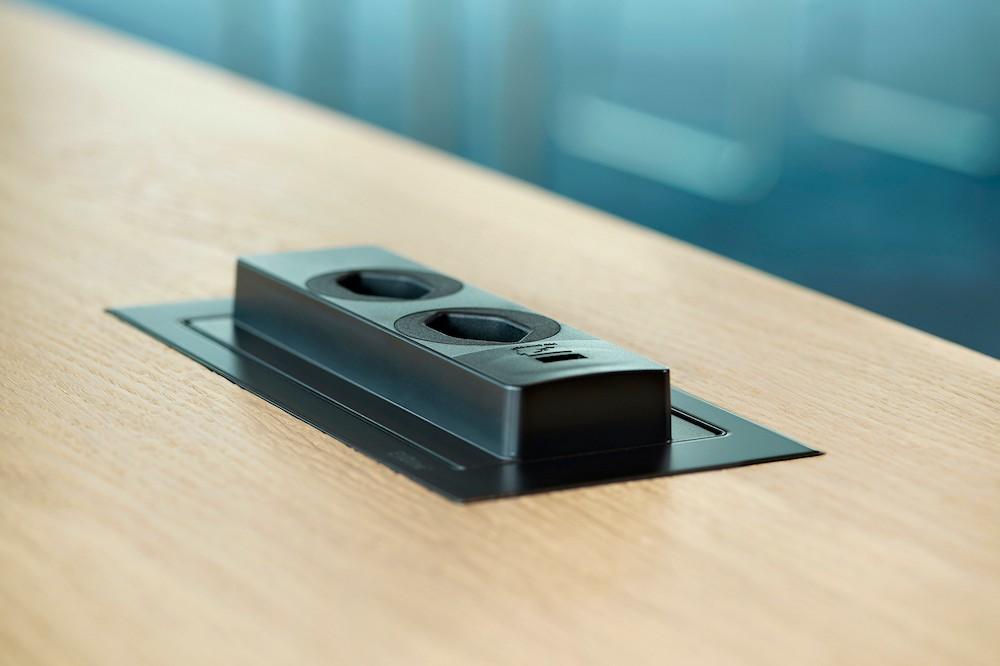 Durch leichtes Antippen gibt das bündig in die Tischplatte eingebaute Elektrifizierungselement zwei Steckdosen sowie einen USB-Charger frei. Abbildung: Schulte Elektrotechnik
